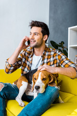 handsome cheerful man talking on smartphone and petting beagle dog