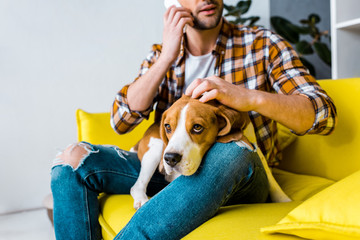 cropped view of man talking on smartphone and petting dog