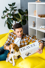 surprised young man reading travel newspaper and sitting on sofa with cute dog