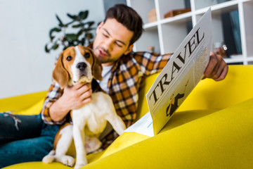 selective focus of happy man reading travel newspaper while sitting on sofa with beagle dog