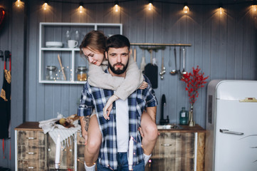 Young hipster stylish caucasian couple cooking, hugging in modern cozy kitchen. Happiness, freedom, family concept