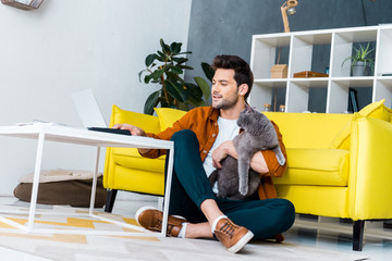 handsome smiling man using laptop while sitting on floor with british shorthair cat