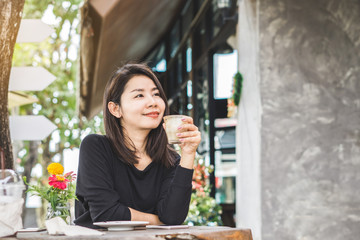 young beautiful Asian woman  sitting at coffee shop hand holding coffee glass