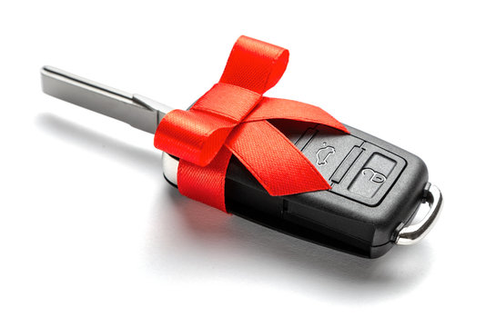 Gift Car keys with remote control alarm with red ribbon with bow. Isolated on white background.