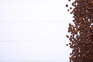 Natural coffee beans on white wooden background