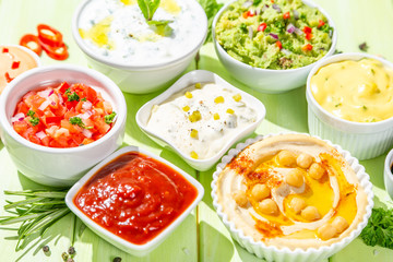 Selection of sauces in white bowls on white bowls, top view