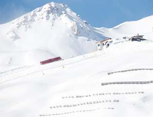 Avalanche protections are seen in front of a train of the Parsennbahn cog railroad in snow-covered landscape near Davos