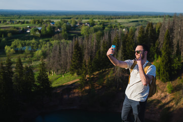 Handsome man shooting selfie in the nautre. Hiking trip. Mountaineering moments. Shooting beautiful views of forest landscapes. In harmony with nature. Sports and fun outdoors