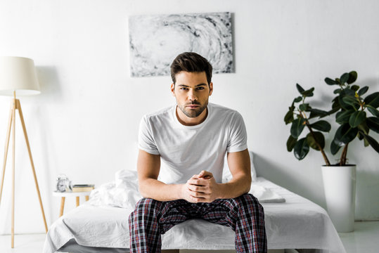 handsome confident man in pajamas sitting on bed at home
