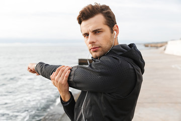 Image of caucasian sportsman 30s in black sportswear and earphones, working out at seaside