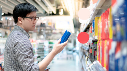 Asian man shopper choosing fizzy drink or carbonated soft drink in can package from shelf in supermarket or grocery store. Shopping sugary product. Unhealthy lifestyle.
