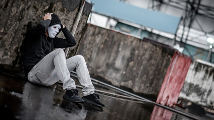 Mystery hoodie man in white mask feeling stressed sitting in the rain on rooftop of abandoned building. Bipolar disorder or Major depressive disorder. Depression concept