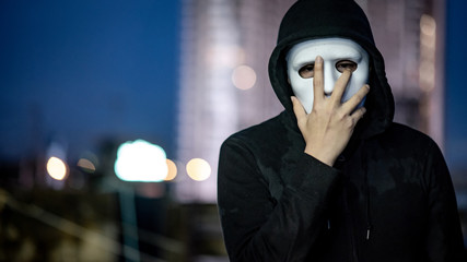 Mystery hoodie man in white mask standing on rooftop of abandoned building during the twilight time. Bipolar disorder or Major depressive disorder. Depression concept