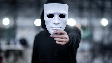 Mystery hoodie man with black mask holding white mask in his hand. Anonymous social masking or bipolar disorder concept.