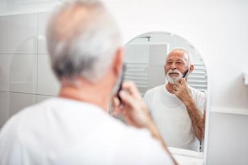 Handsome senior man grooming his beard in the bathroom.