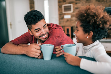 Portrait of a happy young father drinking tea with his daughter at home.