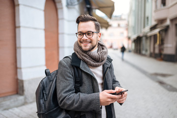 Smiling young man with smartphone in  the city with backpack wearing winter clothes.