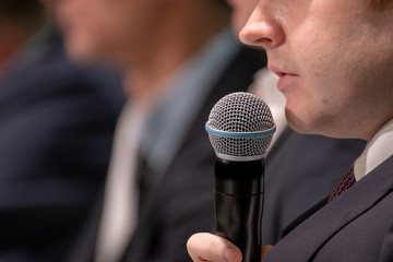 Man speaks, holding a microphone