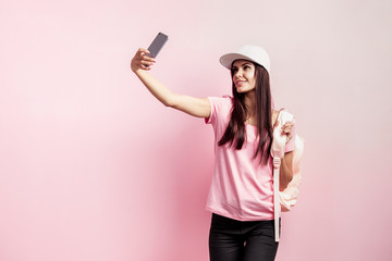 Beautiful girl in white cap and with a backpack on her shoulders dressed in pink t-shirt and black jeans is doing selfie on the pink background in the studio