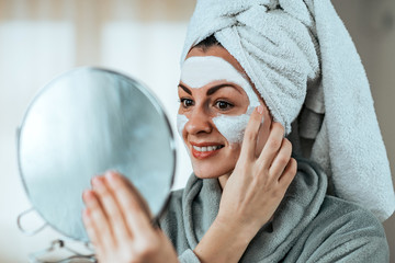 Smiling woman holding a mirror in hand and applying cosmetic facial mask, close-up.