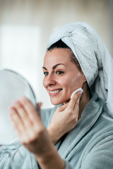 Beautiful woman cleaning her face with cotton pad, holding a mirror.