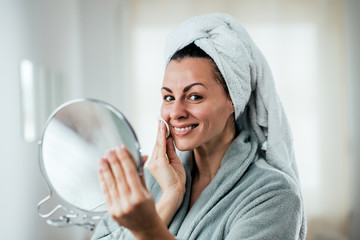 Skincare and beauty concept. Smiling woman cleaning face with cotton pad.