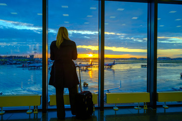 Woman is standing by the window at the airport