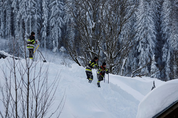 Members of the fire brigade shovel snow on a rooftop after heavy snowfall in the village of Ramsau