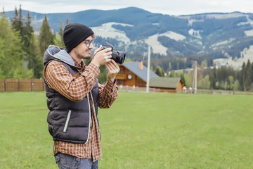 A young boy travels in the mountains with a camera