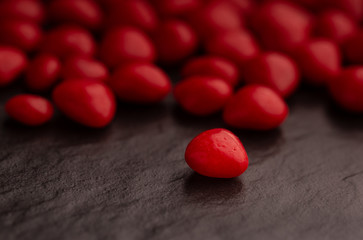 Close up on a red cinnamon heart shaped candy on dark slate