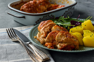 Oven-baked chicken breast with mozzarella and tomatoes, served with potatoes.