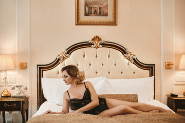 Fashionable and beautiful brunette model girl with bright makeup and with perfect sexy body in stylish black lingerie posing on the bed at the luxury vintage interior