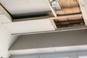 Leaves of the drywall fixed to the wooden frame with screws. Construction walls and suspended ceiling with drywall in a house. Making LED lightning on a ceiling