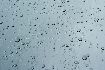 Rain drops on a window glass surface against a dark background of stormy sky.