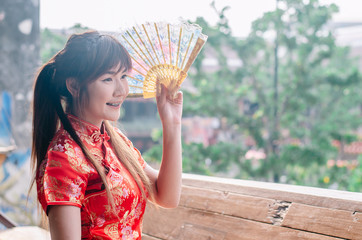 Portrait beautiful young woman smile wear cheongsam deep red dress holding a fan looking outside. Festivities and Celebration concept