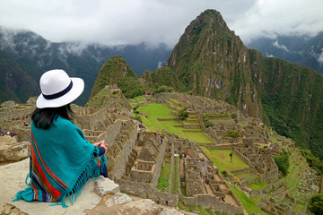 Female Traveler Sitting on the Cliff Looking at the Inca ruins of Machu Picchu, UNESCO World Heritage Site in Cusco Region, Urubamba Province, Peru