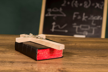 A crucifix on a book against the background of a chalkboard