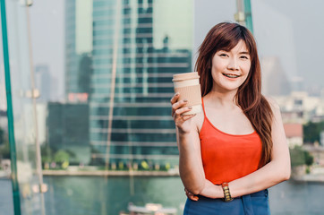 Smiling young woman standing at bangkok skyline with a cup of coffee after working in the evening.