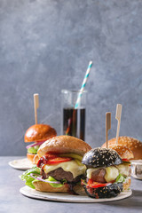Variety of homemade classic and mini burgers in wheat and black buns with beef and veal cutlets, melted cheese and vegetables on white ceramic board over grey blue table. With glass of cola.