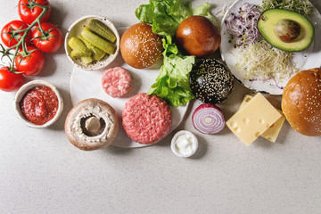 Ingredients for cooking homemade traditional and vegan hamburgers. Meat beef burger, cheese, avocado, portobello, tomato, black and white buns, salad, cucumbers. Grey background. Top view, space.
