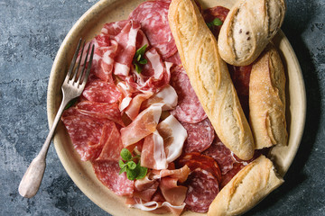 Antipasto meat platter assorti of sliced jamon, salami, chorizo sausage in ceramic plate with bread over blue texture background. Flat lay, close up