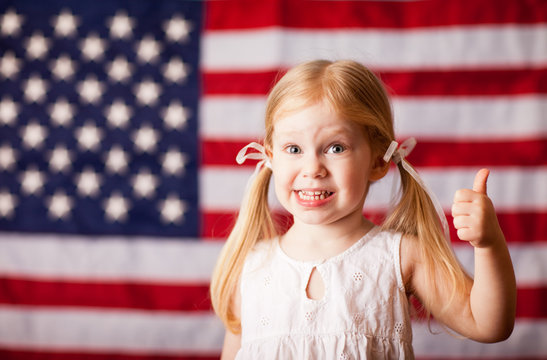 Happy Little Girl Giving Thumbs Up by American Flag