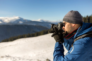 Hiker man tourist photographer in warm clothing with backpack and camera taking picture of snowy valley and woody mountain peaks landscape under blue sky on sunny winter cold day.