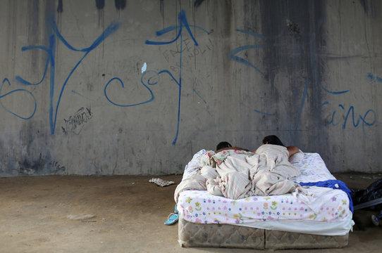 Venezuelan couple sleeps near a bus terminal in Manaus
