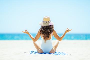 woman doing yoga while sitting on striped towel on seashore
