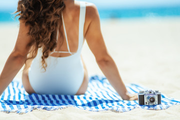 Closeup on photo camera and woman sitting on a striped towel