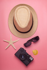 hat, starfish, shell, camera, sunglasses on pink background, travel concept, vertical photo