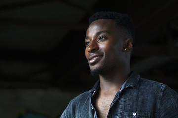 young man with earring portrait shirt dark studio smiling portrait