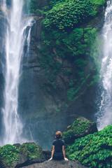 Young woman posing on a great Sekumpul waterfall in the deep rainforest of Bali island, Indonesia.