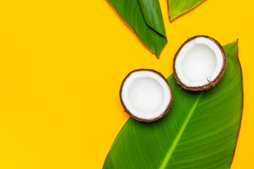 Wall Mural - Ripe coconut and tropical leaves on yellow colored background, minimal flat lay style top view. Pop art design, creative summer and food concept. Tropical fruit whole and half abstract background